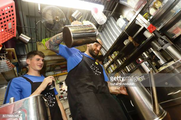 Tommaso Berni of FC Inter Milan learns to prepare the local coffee as teammate Federico Valietti looks on during a International Champions Cup Inter...
