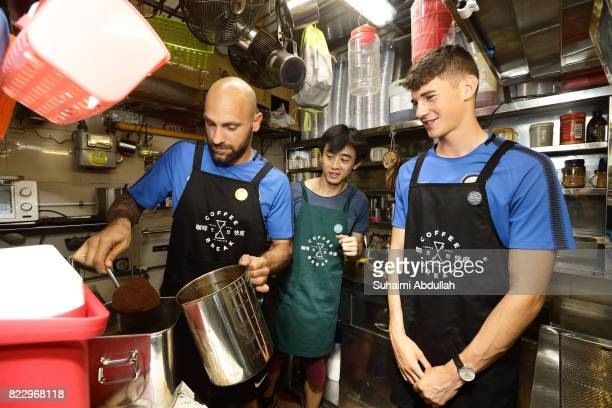Tommaso Berni of FC Inter Milan learns to prepare the local coffee as teammate Federico Valietti and Jack Sai owner of Coffee Break looks on during a...