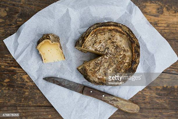 Tomme de Savoie cheese and knife on greaseproof paper on wooden table
