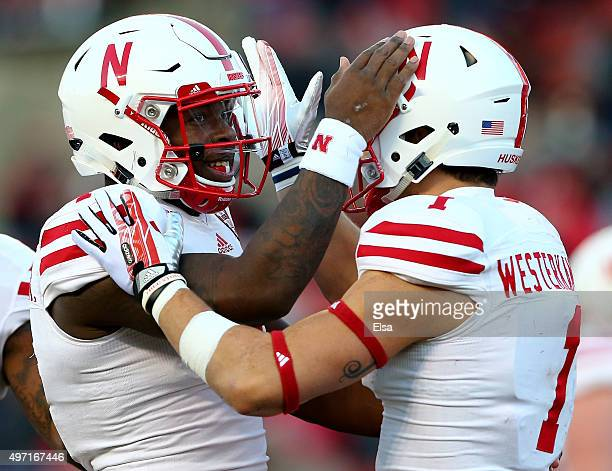 Tommy Armstrong Jr #4 of the Nebraska Cornhuskers congratulates teammate Jordan Westerkamp after he scored a touchdown in the first quarter against...
