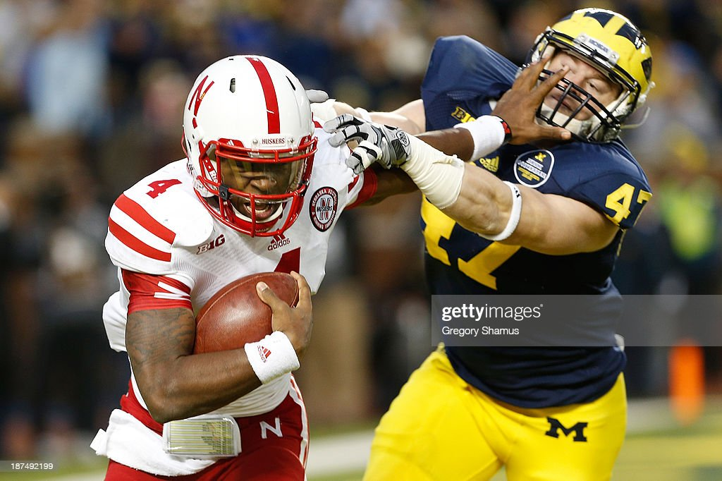 Tommy Armstrong Jr. #4 of the Nebraska Cornhuskers stiff arms Jake Ryan #47 of the Michigan Wolverines in the second quarter at Michigan Stadium on November 9, 2013 in Ann Arbor, Michigan.