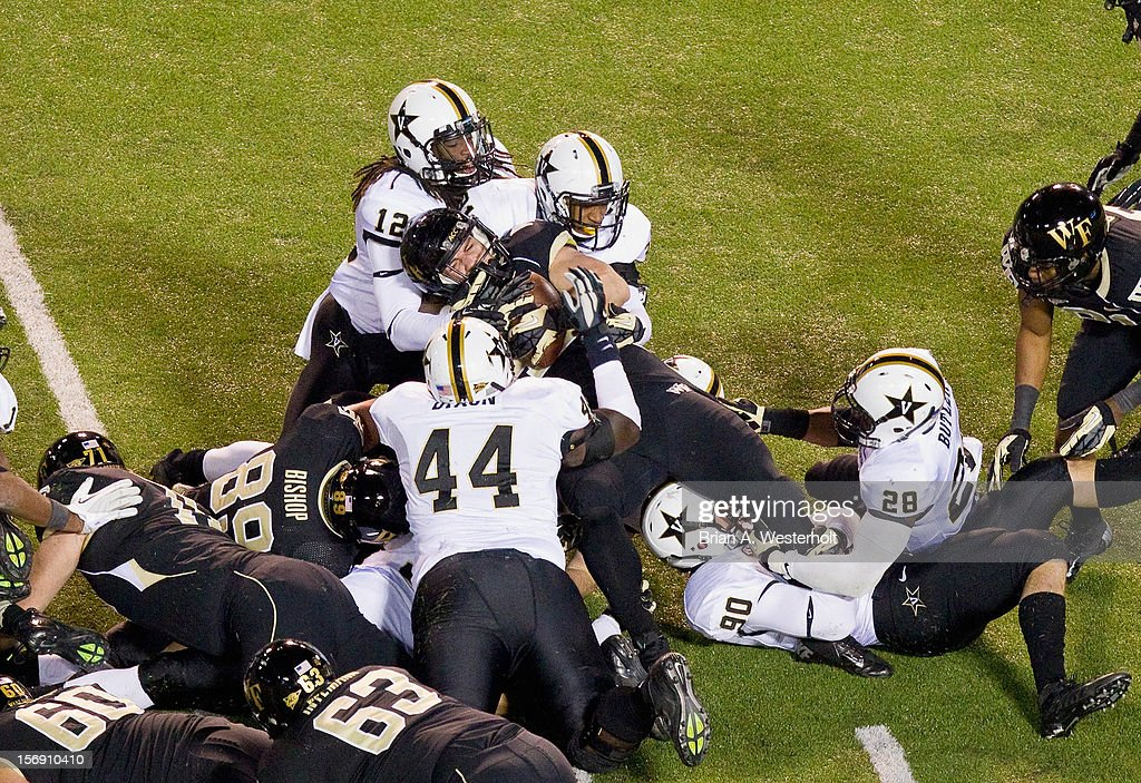 Tommy Bohanon #42 of the Wake Forest Demon Deacons is stopped short of a first down by Walker May #90 and Javon Marshall #31 of the Vanderbilt Commodores at BB&T Field on November 24, 2012 in Winston Salem, North Carolina. The Commodores defeated the Demon Deacons 55-21.