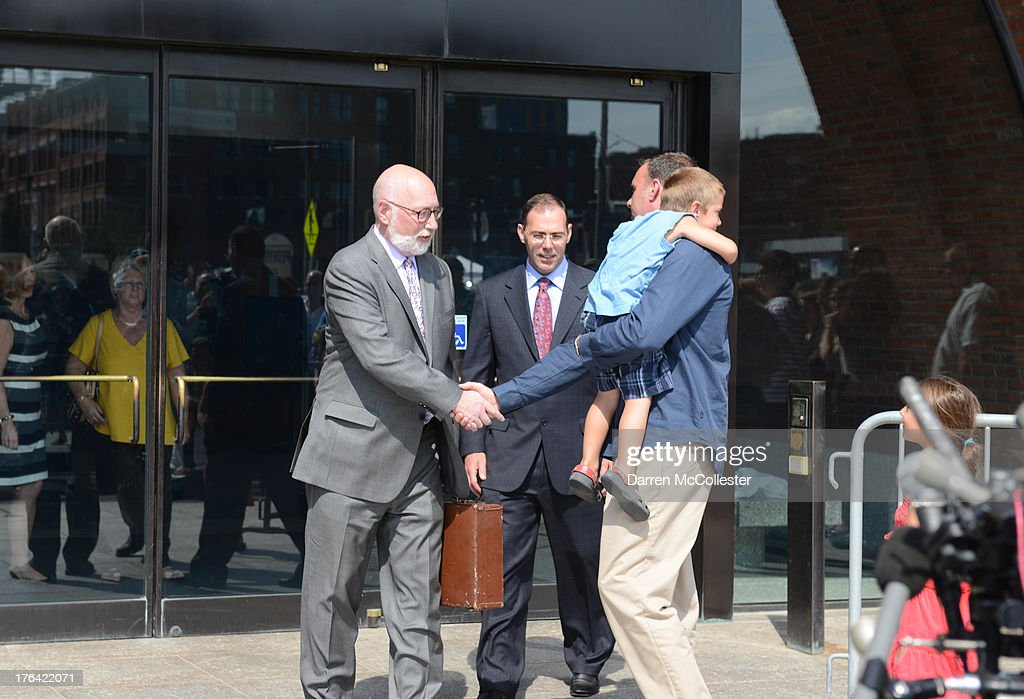 Tommy Donohue son of murder victim Michael Donahue shakes hands with defense lawyers JW Carney and Hank Brennan while holding his godson Alex after...
