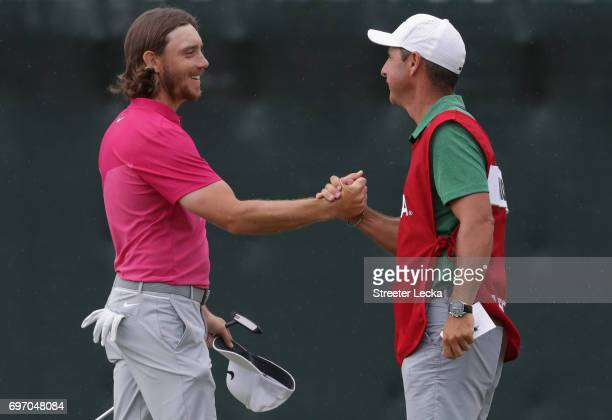 Tommy Fleetwood of England and Richard Elliott caddie for Brooks Koepka shake hands after finishing on the 18th green during the third round of the...