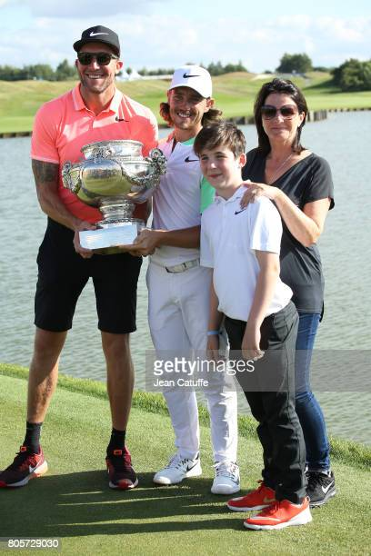 Tommy Fleetwood of England celebrates winning the tournament with his caddy Ian Finnis his girlfriend Clare Craig and her son during the trophy...