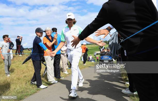 Tommy Fleetwood of England high 5's supporters as he walks to the 14th tee after making a berdie on the 13th during day four of the HNA Open de...