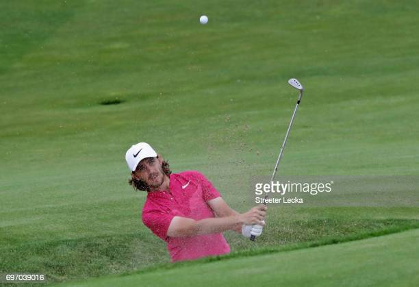 Tommy Fleetwood of England plays his shot from a bunker on the 14th hole during the third round of the 2017 US Open at Erin Hills on June 17 2017 in...