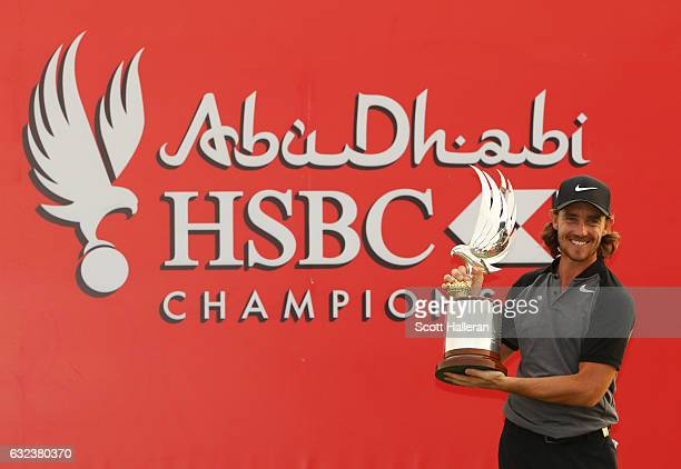 Tommy Fleetwood of England poses for photographs with the trophy after winning the tournament during the final round of the Abu Dhabi HSBC...