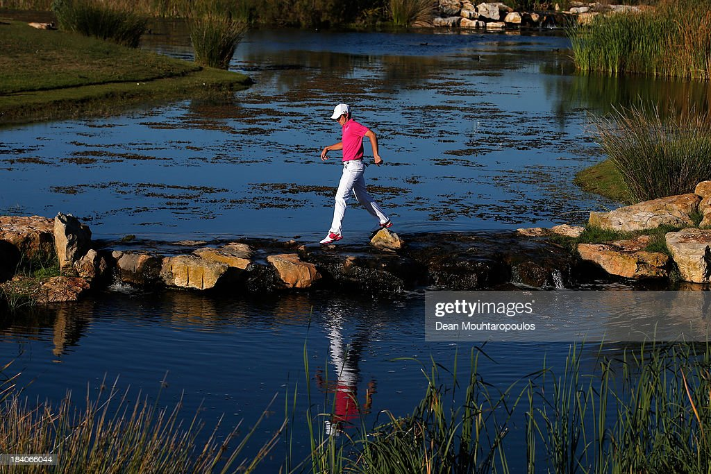 Tommy Fleetwood of England uses some stepping stones to cross the water from the 17th tee to the 16th green during the second round of the Portugal...