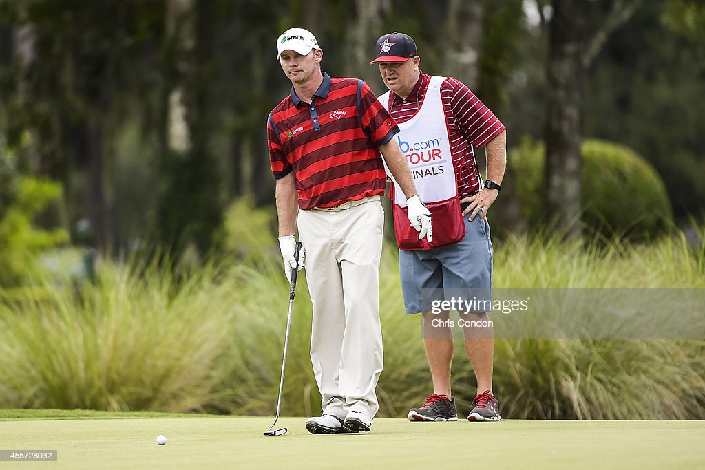 Tommy Gainey lines up a putt with his caddie on the ninth hole green during the second round of the Webcom Tour Championship at TPC Sawgrass Dye's...