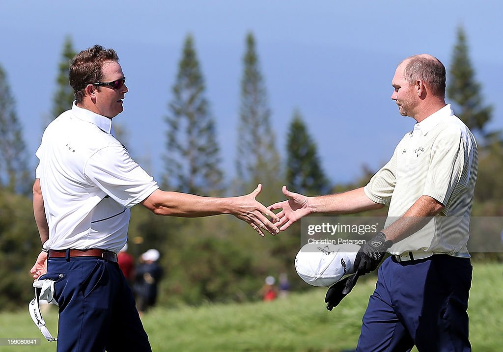 Tommy Gainey (R) skates hands with Charlie Beljan on the ninth hole green following the replay of the first round of the Hyundai Tournament of Champions at the Plantation Course on January 7, 2013 in Kapalua, Hawaii.