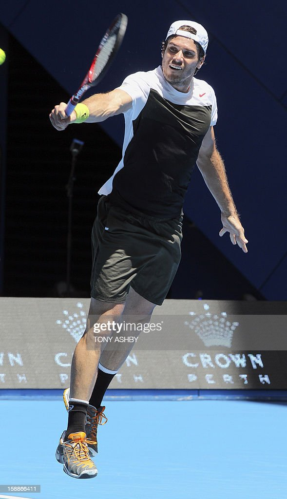 Tommy Haas of Germany hits a high return against Andreas Seppi of Italy during their seventh session men's singles match on day five of the Hopman Cup tennis tournament in Perth on January 2, 2013. AFP PHOTO / Tony ASHBY USE