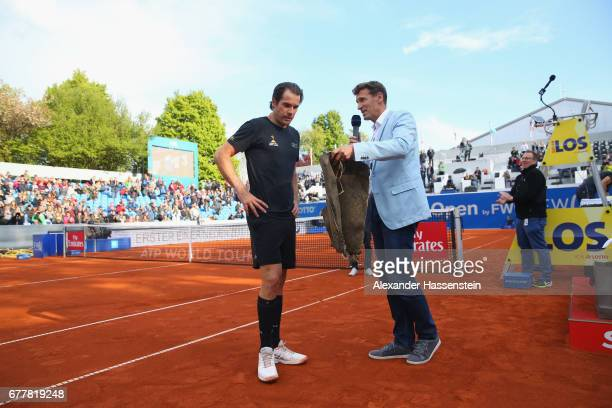 Tommy Haas of Germany leaves the centre court in a traditional Bavarian leather pants next to tournament director Patrick Kuehnen after his 2 round...