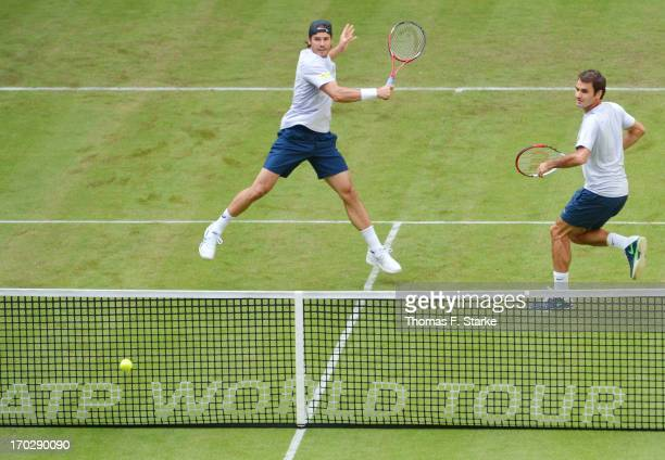 Tommy Haas of Germany plays a forehand while Roger Federer of Switzerland looks on during their first round doubles match against Jurgen Melzer of...