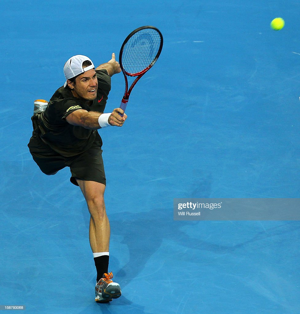 <a gi-track='captionPersonalityLinkClicked' href=/galleries/search?phrase=Tommy+Haas&family=editorial&specificpeople=171956 ng-click='$event.stopPropagation()'>Tommy Haas</a> of Germany returns a volley in his singles match against Bernard Tomic of Australia during day one of the Hopman Cup at Perth Arena on December 29, 2012 in Perth, Australia.