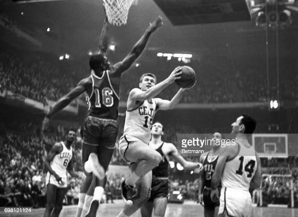 Tommy Heinsohn of the Celtic's breaks past Al Attles of the Warriors #16 to layup for a basket in the 1st quarter playoff