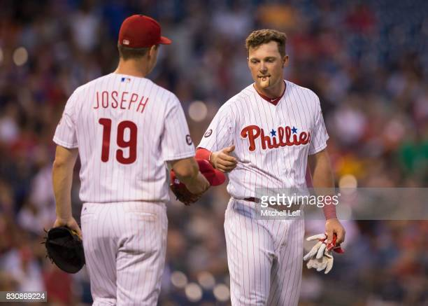 Tommy Joseph of the Philadelphia Phillies hands Rhys Hoskins of the Philadelphia Phillies his glove and hat against the New York Mets at Citizens...
