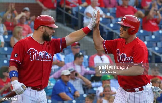 Tommy Joseph of the Philadelphia Phillies high fives Cameron Rupp after scoring a run in the seventh inning during a game against the Miami Marlins...