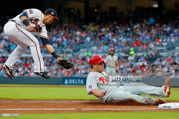 Tommy Joseph of the Philadelphia Phillies slides safely into third base under Rio Ruiz of the Atlanta Braves on a deep out by Maikel Franco in the...