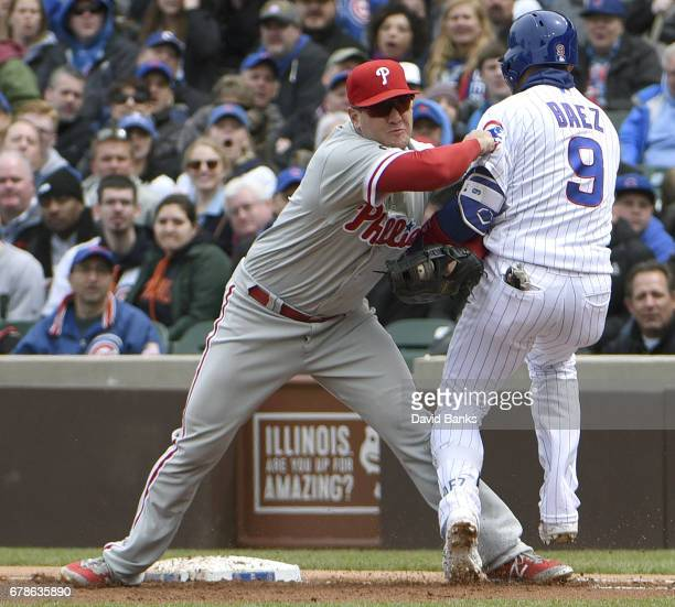 Tommy Joseph of the Philadelphia Phillies tags out Javier Baez of the Chicago Cubs at first base during the second inning on May 4 2017 at Wrigley...