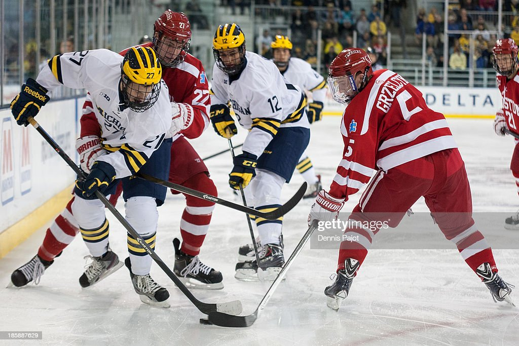 Tommy Kelley #22 and Matt Grzelcyk #5 of the Boston University Terriers battles against Alex Guptill #27 and Boo Nieves #12 of the Michigan Wolverines on October 25, 2013 at Yost Ice Arena in Ann Arbor, Michigan.