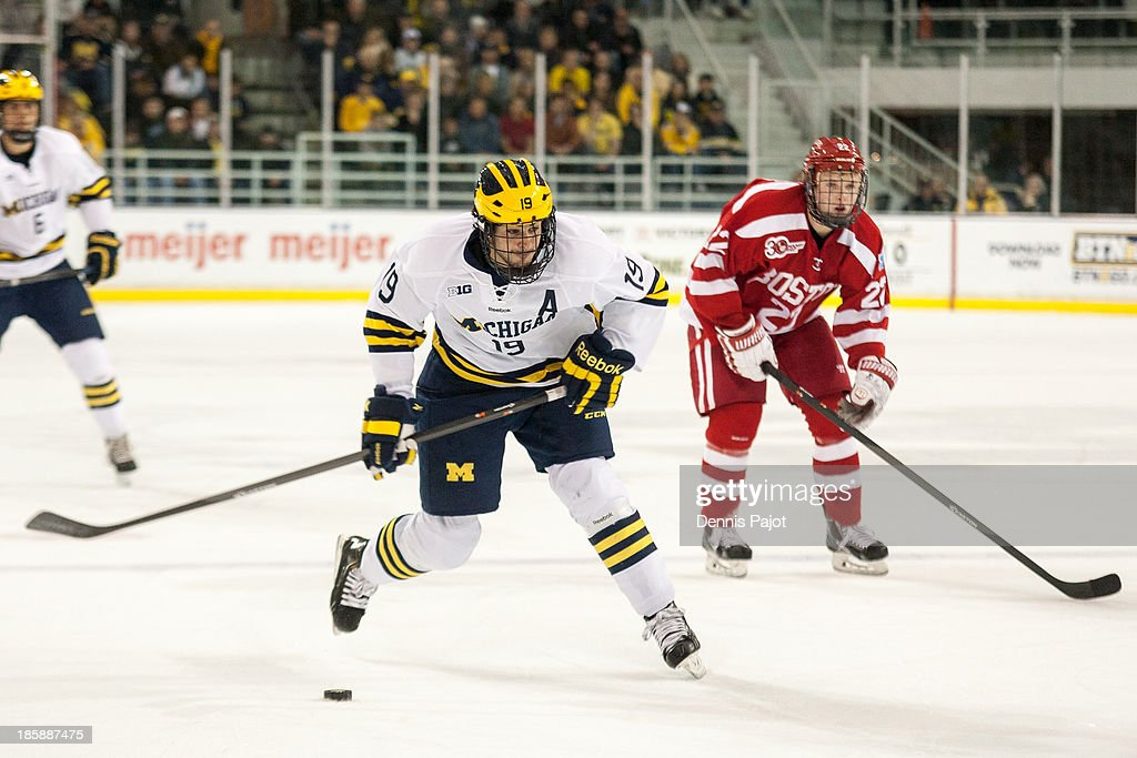 Tommy Kelley #22 of the Boston University Terriers challenges Derek DeBlois #19 of the Michigan Wolverines on October 25, 2013 at Yost Ice Arena in Ann Arbor, Michigan.