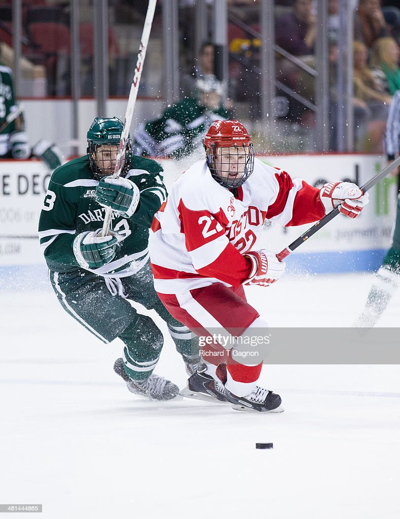 Tommy Kelley #22 of the Boston University Terriers skates against Brett Patterson #13 of the Dartmouth College Big Green during NCAA hockey action at Agganis Arena on January 8, 2014 in Boston, Massachusetts.