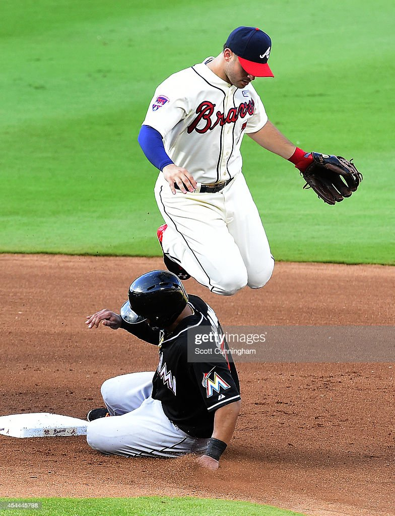 Tommy La Stella #7 of the Atlanta Braves turns a fourth inning double play against Donovan Solano #17 of the Miami Marlins at Turner Field on August 31, 2014 in Atlanta, Georgia.