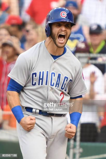 Tommy La Stella of the Chicago Cubs celebrates scoring on a single by Javier Baez during a baseball game against the Washington Nationals at...