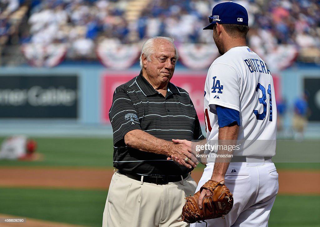 Tommy Lasorda shakes hands with Drew Butera of the Los Angeles Dodgers after he threw out the first pitch prior to the start of Game One of the...