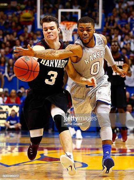 Tommy McCarthy of the Harvard Crimson and Frank Mason III of the Kansas Jayhawks compete for a loose ball during the 1st half of the game at Allen...