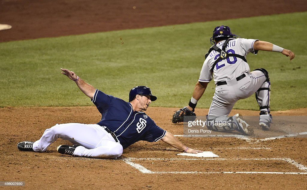 Tommy Medica #14 of the San Diego Padres scores ahead of the throw to Wilin Rosario #20 of the Colorado Rockies during the sixth inning of a baseball game at Petco Park September, 23, 2014 in San Diego, California.