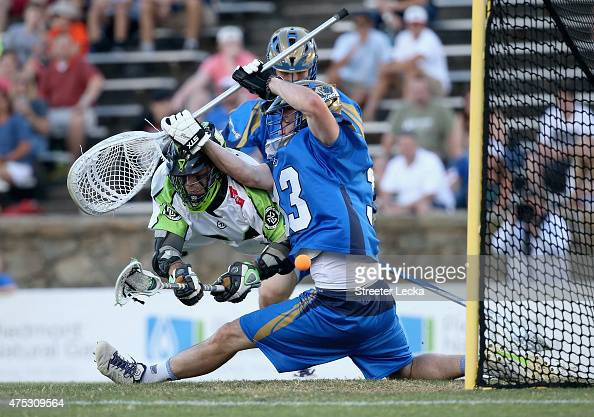 Tommy Palasek of the New York Lizards scores against Pierce Bassett of the Charlotte Hounds during their game at American Legion Memorial Stadium on...
