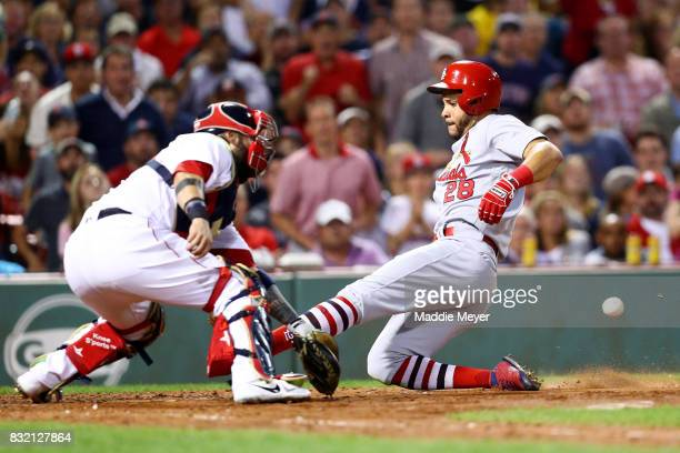 Tommy Pham of the St Louis Cardinals scores a run past Sandy Leon of the Boston Red Sox during the sixth inning at Fenway Park on August 15 2017 in...