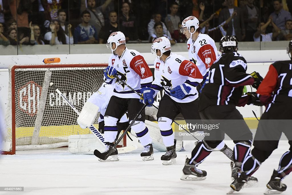 Tommy Pyatt of Geneve-Servette on the right has shot the puck in the net while goalie Jean-Philippe Lamoureux is hidden , while # 6 <a gi-track='captionPersonalityLinkClicked' href=/galleries/search?phrase=Gerhard+Unterluggauer&family=editorial&specificpeople=2415907 ng-click='$event.stopPropagation()'>Gerhard Unterluggauer</a>, # 8 Rusian Gelfanov, # 22 Adis Alagic of Villach SV are just looking on during the Champions Hockey League group stage game between Geneve-Servette and Villach SV on August 23, 2014 in Geneva, Switzerland.