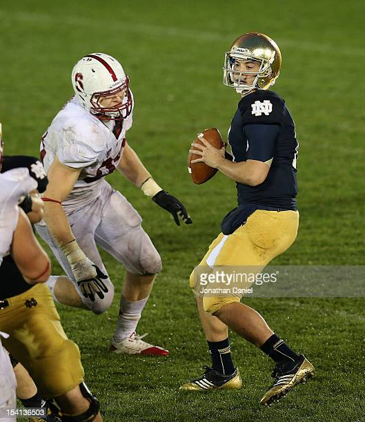 Tommy Rees of the Notre Dame Fighting Irish looks for a receiver during overtime as Trent Murphy of the Standford Cardinal applies pressure at Notre...