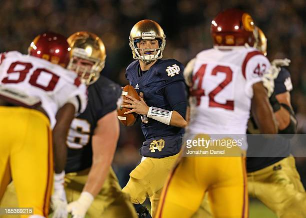 Tommy Rees of the Notre Dame Fighting Irish looks for a receiver as George Uko and Devon Kennard of the University of Southern California Trojans...