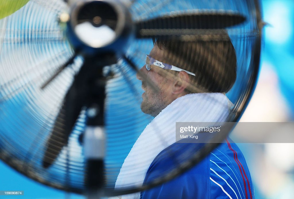 Tommy Robredo of Spain rests next to a fan in between games in his first round match against John Millman of Australia during day three of Sydney International at Sydney Olympic Park Tennis Centre on January 8, 2013 in Sydney, Australia.