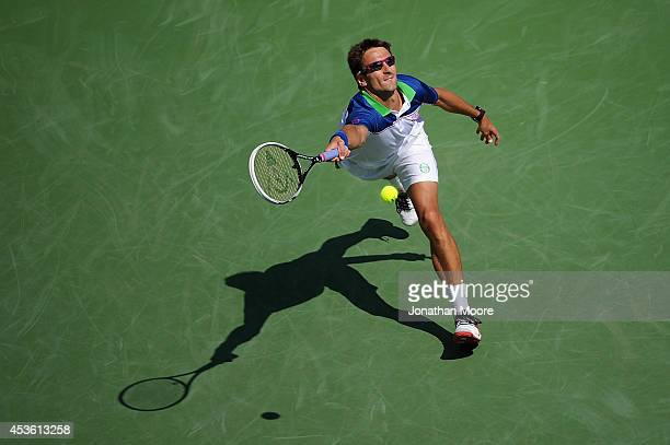 Tommy Robredo of Spain returns to Novak Djokovic of Serbia during a match on day 6 of the Western Southern Open at the Linder Family Tennis Center on...