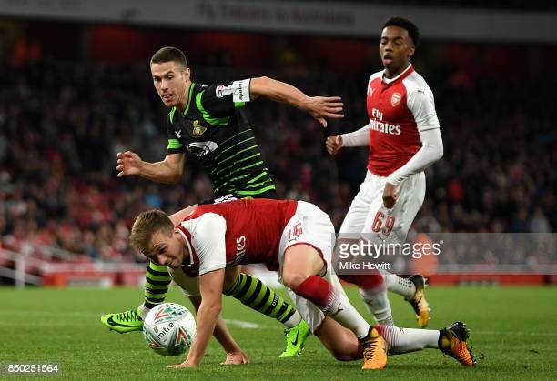 Tommy Rowe of Doncaster Rovers and Rob Holding of Arsenal battle for possession during the Carabao Cup Third Round match between Arsenal and...