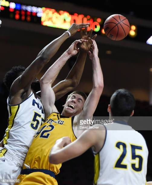 Tommy Rutherford of the UC Irvine Anteaters reaches for a rebound agianst Ruben Fuamba and Brooks Debisschop of the Northern Arizona Lumberjacks and...
