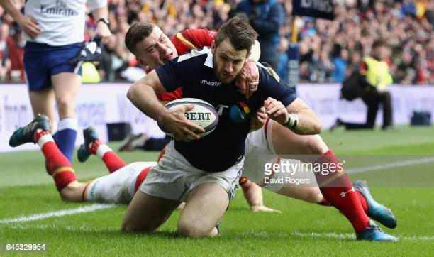 Tommy Seymour of Scotland goes past Liam Williams and Scott Williams of Wales to score his team's first try during the RBS Six Nations match between...