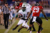Tommy Shuler of the Marshall Thundering Herd carries as Paris Logan of the Northern Illinois Huskies defends during the first half of the game at FAU...