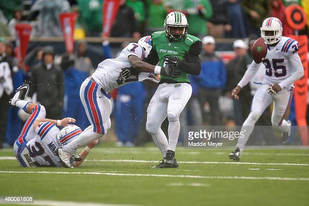 Tommy Shuler of the Marshall Thundering Herd fumbles the fall while being tackled by Xavier Woods of the Louisiana Tech Bulldogs during the fourth...