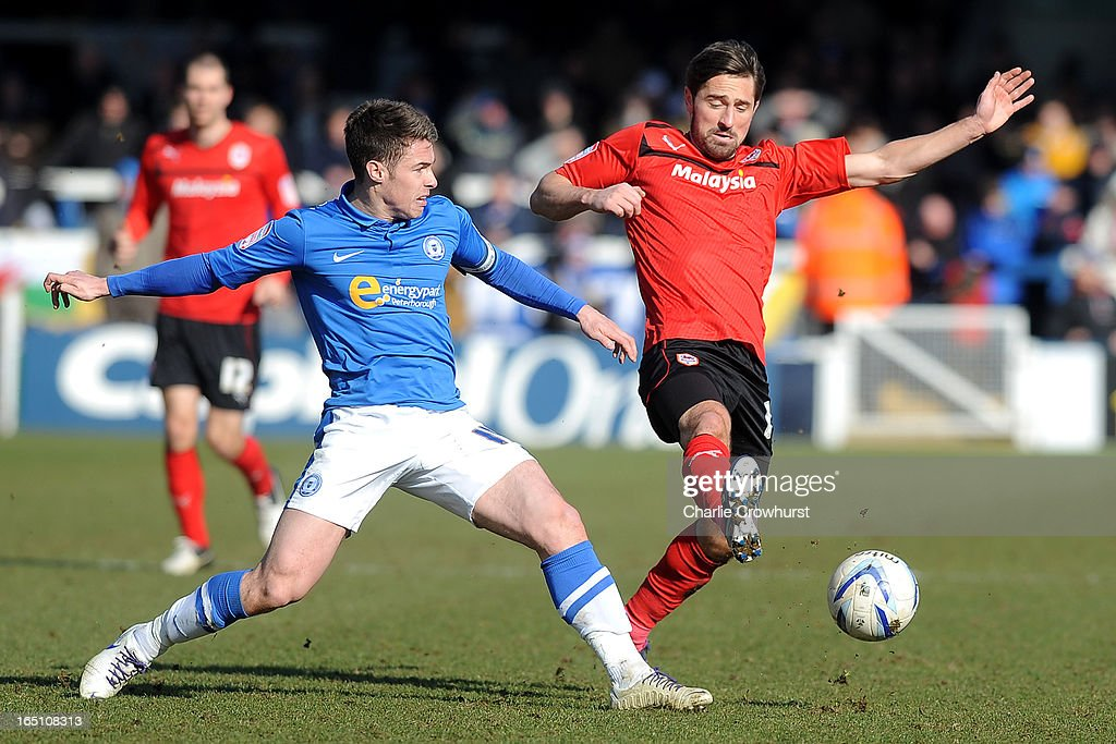 Tommy Smith of Cardiff City goes in for the ball with Peterborough's Tommy Rowe during the npower Championship match between Peterborough United and Cardiff City at London Road on March 30, 2013 in Peterborough, England,