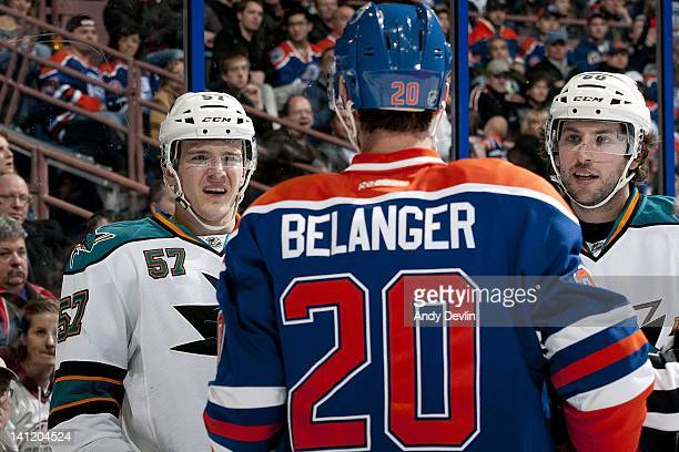 Tommy Wingels and Jason Demers of the San Jose Sharks taunt Eric Belanger of the Edmonton Oilers at Rexall Place on March 12 2012 in Edmonton Alberta...
