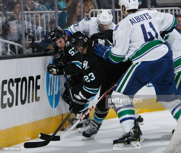 Tommy Wingels and Scott Gomez of the San Jose Sharks battle for the puck against Andrew Alberts of the Vancouver Canucks in Game Four of the Western...