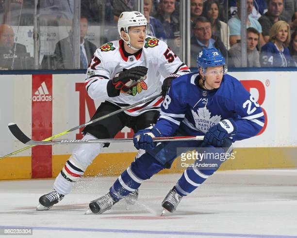 Tommy Wingels of the Chicago Blackhawks skates against Connor Brown of the Toronto Maple Leafs in an NHL game at the Air Canada Centre on October 9...