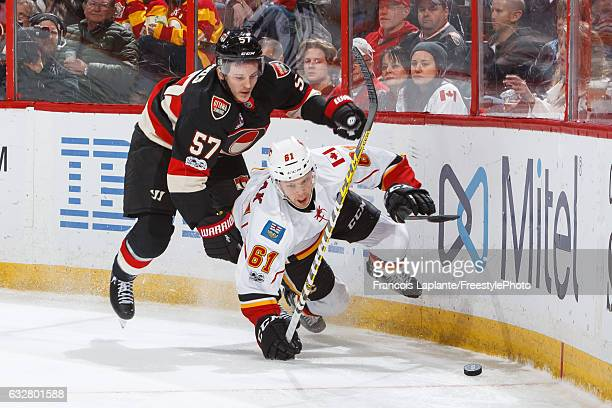 Tommy Wingels of the Ottawa Senators battles for a loose puck against Brett Kulak of the Calgary Flames during an NHL game at Canadian Tire Centre on...