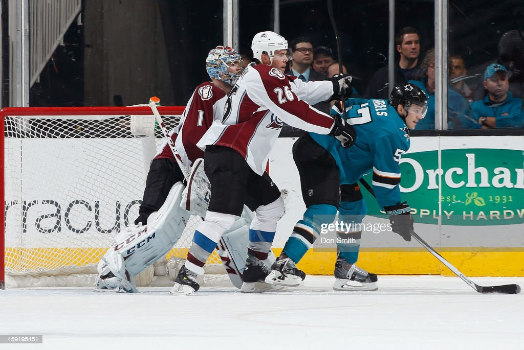 Tommy Wingels #57 of the San Jose Sharks battles for positioning in front of the net against Semyon Varlamov #1 and Paul Stasty #26 of the Colorado Avalanche during an NHL game on December 23, 2013 at SAP Center in San Jose, California.